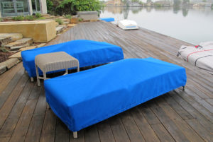 Patio furniture in back yard with tailored blue canvas covers on chaise